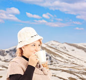 Mature smiling woman drinking a tea and posing outside in snowy Stock Photography