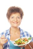 Mature smiling woman eating salad. Isolated on white Royalty Free Stock Image