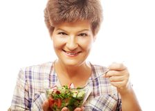 Mature smiling woman eating salad. Isolated on white Stock Photo