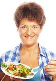 Mature smiling woman eating salad. Isolated on white Stock Photos