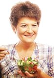 Mature smiling woman eating salad. Isolated on white Stock Image