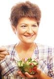 Mature smiling woman eating salad Stock Image
