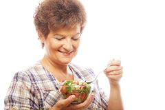 Mature smiling woman eating salad. Isolated on white Royalty Free Stock Images