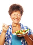 Mature smiling woman eating salad. M isolated on white Stock Photo
