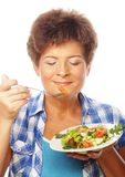 Mature smiling woman eating salad. M isolated on white Stock Images