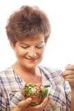 Mature smiling woman eating salad. M isolated on white Royalty Free Stock Photography