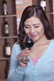 Mature smiling woman with eyes closed smelling a glass of red wine Stock Photos