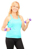 Mature smiling woman lifting up dumbbells Royalty Free Stock Photos