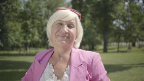 Mature smiling woman looking at camera smiling standing in summer park. Leisure outdoors. Mature caucasian lady resting. Positive old woman in pink dress looking stock video footage