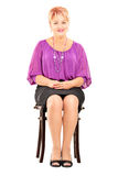 Mature smiling woman sitting on a wooden chair Stock Photography