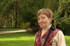 Mature smiling woman in summer park. An elderly woman in the summer park Royalty Free Stock Photography