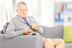 Mature on sofa measuring sugar level in blood using glucometer a royalty free stock photography