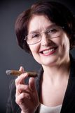 Mature solid businesswoman with cigar, smiling Royalty Free Stock Photos