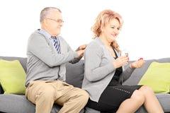 Mature som tar preventivpillerar och maken som ger henne en tillbaka massage Royaltyfri Bild