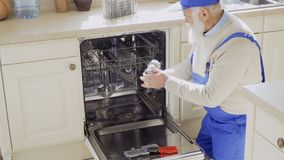 Senior man in blue overalls clean sink of the dishwasher. Mature specialist repairs dishwasher at the kitchen. Old man wearing protective coveralls works as stock footage