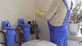 Mature specialist sprays on the pipes with product from rust. Mature specialist sprays oil into a pipes. The worker protects the metal from rust. The master is stock footage