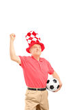 Mature sport fan with hat holding a soccer ball and gesturing Royalty Free Stock Image