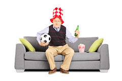 Mature sport fan holding a ball and beer watching sport Stock Photo