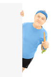Mature sportsman holding a carrot and posing behind panel Stock Images