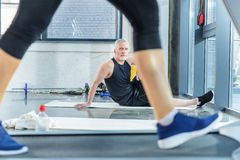 Mature sportsman sitting on yoga mat and looking at woman training on treadmill. Bearded mature sportsman sitting on yoga mat and looking at woman training on Stock Image