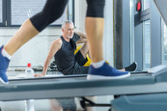 Mature sportsman sitting on yoga mat with towel while woman training on treadmill. Bearded mature sportsman sitting on yoga mat with towel while woman training Stock Photo