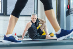 Mature sportsman sitting on yoga mat with towel while woman training on treadmill. Bearded mature sportsman sitting on yoga mat with towel while woman training Royalty Free Stock Photo
