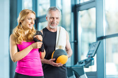 Mature sportsman and sportswoman with towels and ball standing together in gym Stock Image