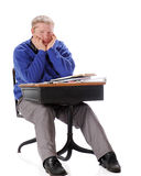 Mature Student Bored. A bored manture man sitting in an old school desk piled with books and papers. On a white background royalty free stock images