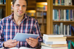 Mature student holding tablet PC in the library. Portrait of a content mature male student holding tablet PC in the library Stock Image