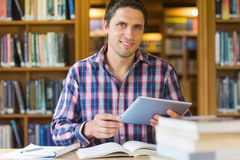 Mature student holding tablet PC in the library. Portrait of a happy mature male student holding tablet PC in the library Stock Photo