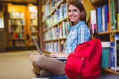 Mature student in the library using laptop Stock Photo