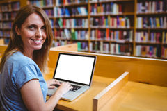 Mature student in the library using laptop Royalty Free Stock Image