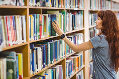 Mature student picking book in library wearing smart watch Stock Photos