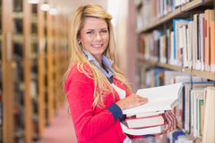 Mature student picking out book in library Stock Images