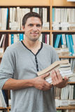 Mature student posing in library holding a pile of books Royalty Free Stock Photography
