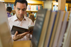 Mature student reading book by shelf in library Royalty Free Stock Images