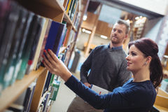 Mature student removing book from shelf. In college library Stock Image