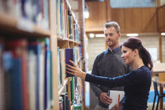 Mature student removing book from shelf. In college library Royalty Free Stock Photos