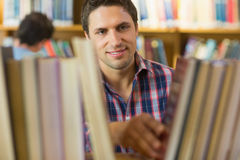 Mature student selecting book from shelf in the library Stock Photos