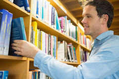 Mature student selecting book from shelf in library Royalty Free Stock Photos