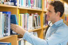 Mature student selecting book from shelf in library Stock Photo