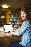 Mature student studying in library with laptop Royalty Free Stock Photo