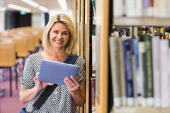 Mature student studying in the library with tablet Stock Images