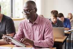 Mature Student Using Digital Tablet In Adult Education Class Stock Photo