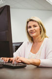 Mature student using laptop looking at camera. In the office royalty free stock image