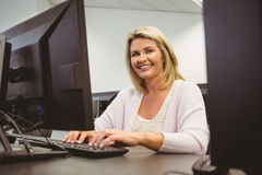 Mature student using laptop looking at camera. In the office royalty free stock photography