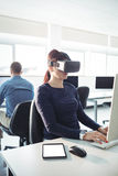 Mature student in virtual reality headset using computer. To help with studying at college Royalty Free Stock Images