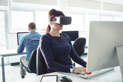 Mature student in virtual reality headset using computer. To help with studying at college Stock Image