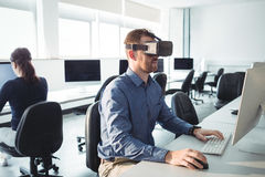 Mature student in virtual reality headset using computer. To help with studying at college Stock Photo