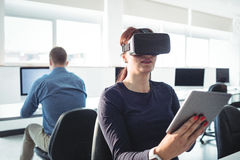 Mature student in virtual reality headset using digital tablet. To help with studying at college Stock Photography